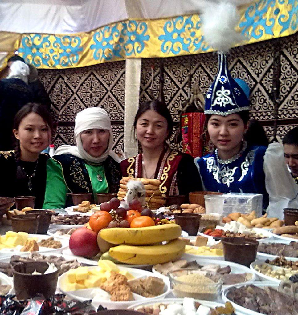 Donne in abiti tradizionali durante il Nauryz. A destra ragazza con Saukele; seconda da sinistra, signora con turbante bianco.